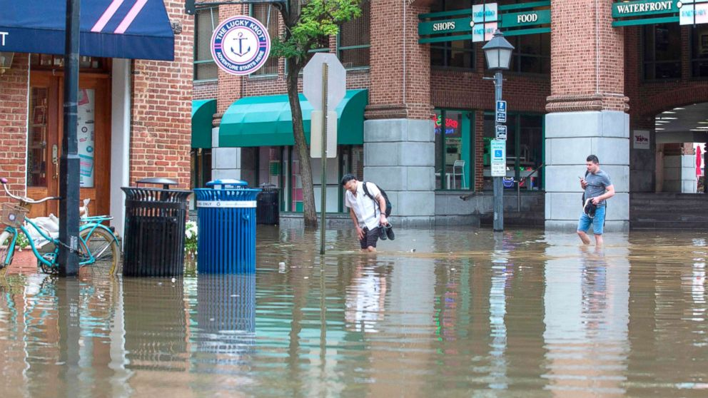 People cross the street as water floods outside buildings in Old Town Alexandria, Va., Sept. 11, 2018. More than a million people were under evacuation orders in the eastern U.S. Tuesday, where powerful Hurricane Florence threatened catastrophic damage to a region popular with vacationers and home to crucial government institutions.