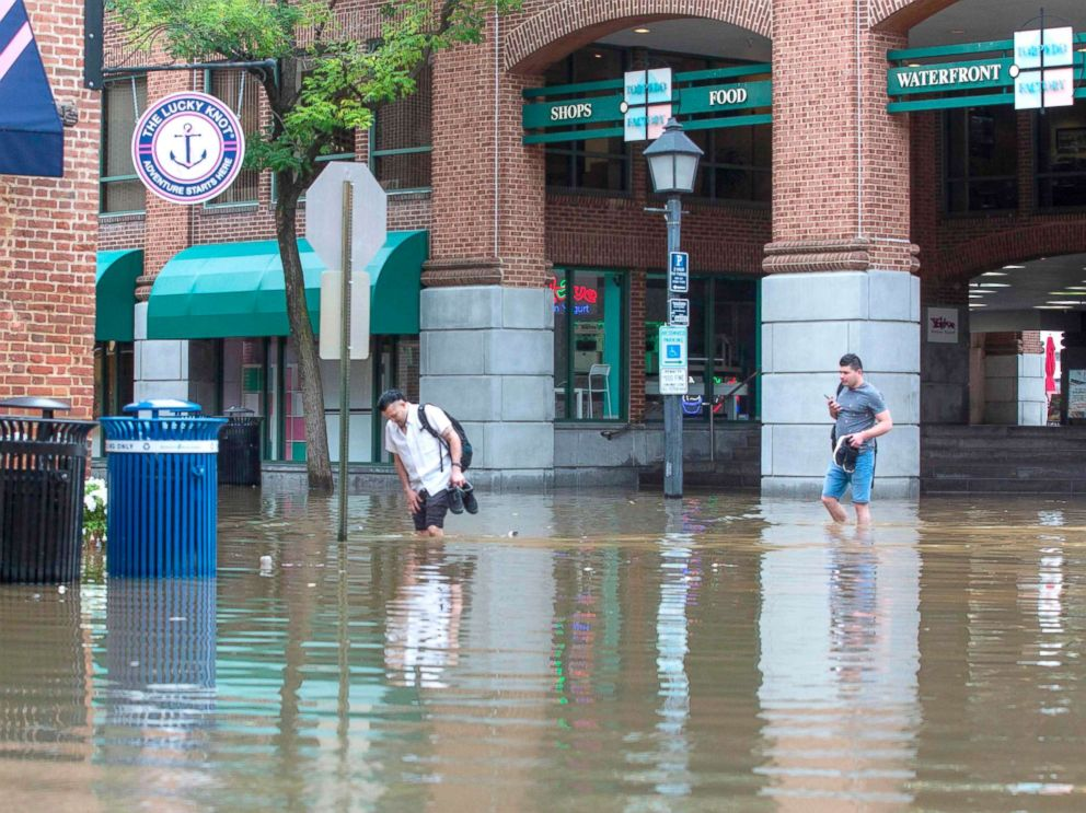 PHOTO: People cross the street as water floods outside buildings in Old Town Alexandria, Va., Sept. 11, 2018.