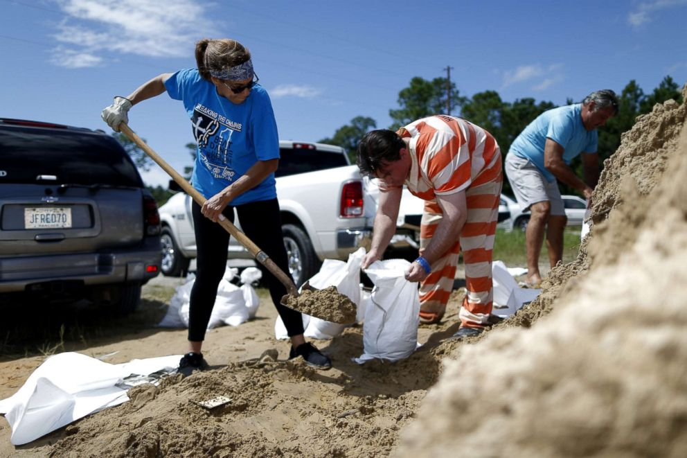 PHOTO: An inmate with the Hancock County Department of Corrections helps Janice Labat fill a bag with sand as Tropical Storm Gordon approaches Bay St. Louis, Mississippi, Sept. 4, 2018.