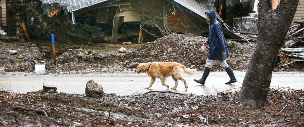PHOTO: Loreen Zakem and Holly go for a daily walk along Camino Viejo Rd. past one of dozens of homes destroyed in a January debris flow along Montecito Creek, March, 21, 2018, in Santa Barbara, Calif.