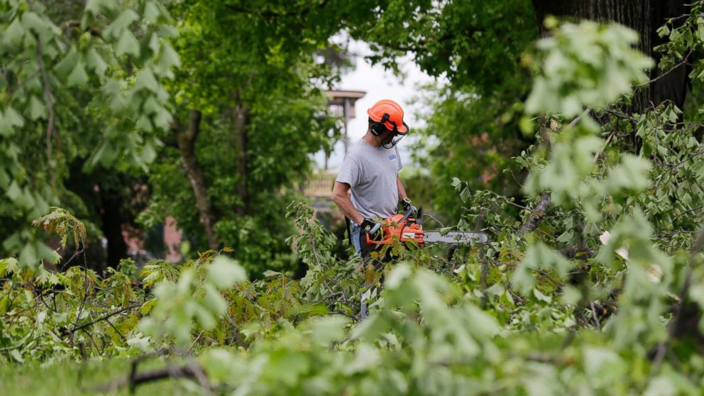 A man clears downed branches and debris on the grounds of Washington's Headquarters State Historic Site in Newburgh, N.Y., May 16, 2018.