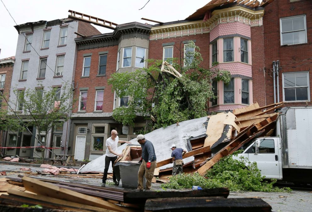 PHOTO: Men work to clear debris out of the street in Newburgh, N.Y., May 16, 2018.