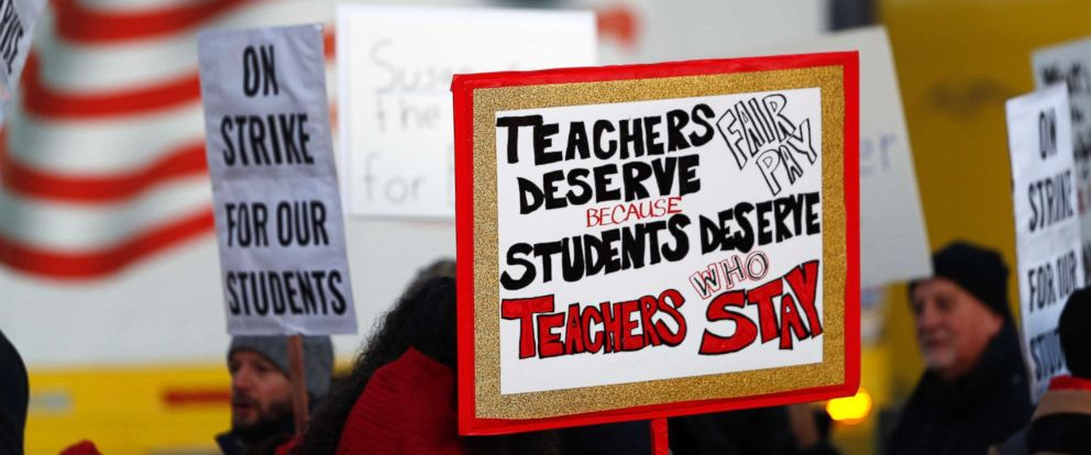 PHOTO: Teachers carry placards as they walk a picket line outside South High School,, Feb. 11, 2019, in Denver.