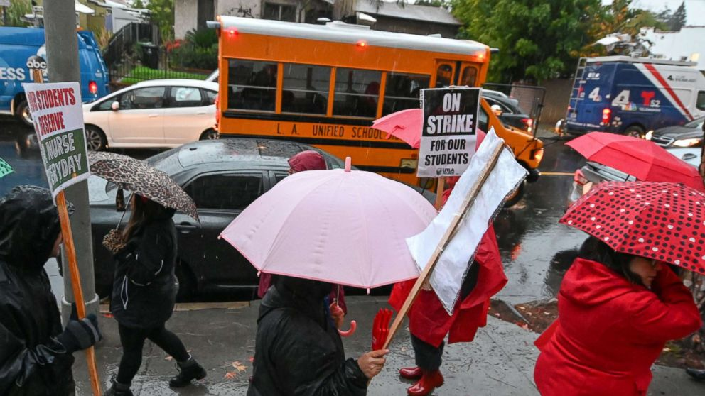 A school bus arrives with students as teachers and their supporters picket outside John Marshall High School in Los Angeles, on the first day of the teachers' strike, Jan. 14, 2019.