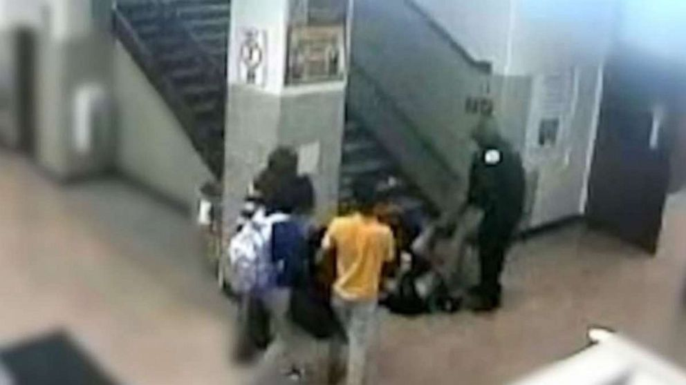 A school resource officer at John Marshall Metropolitan High School in Chicago can be seen dragging a 16-year-old girl down a flight of stairs in a February incident. Two officers were reassigned after the confrontation.
