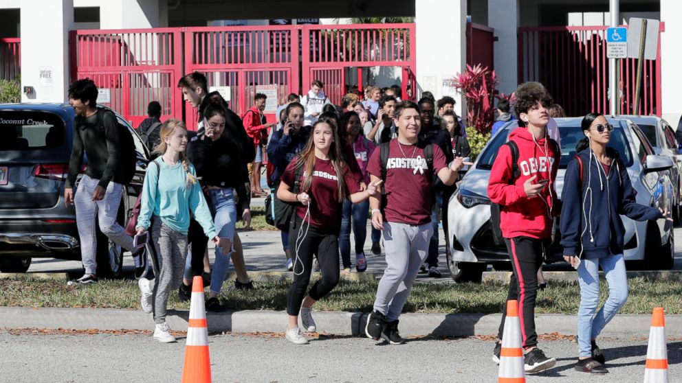 Students walk out of Marjory Stoneman Douglas High School, as part of a nationwide protest against gun violence, March 14, 2018, in Parkland, Fla.