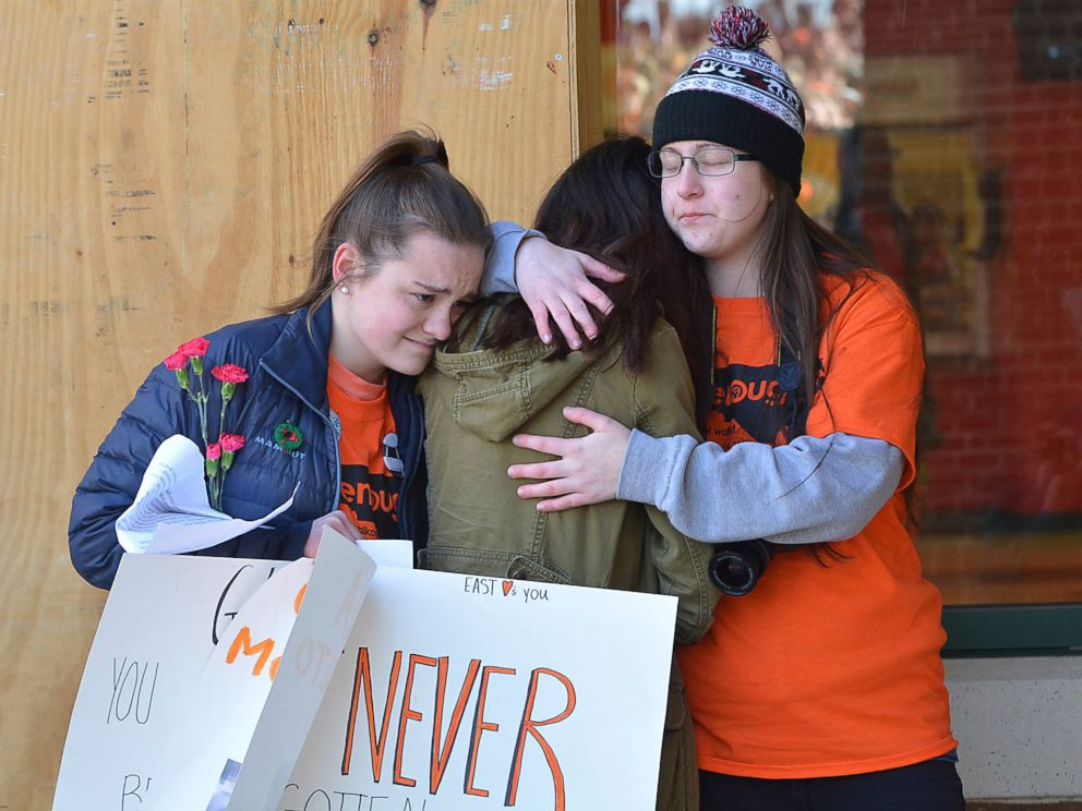 PHOTO: East chapel Hill students hug as they take part in a student walkout on March 14, 2018 in Chapel Hill, N.C.
