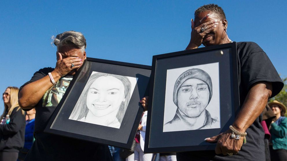 Pat Gibson, left, and Valerie Davis cry while holding pictures of two of the victims killed in the Parkland shooting during the one-month anniversary walkouts to protest gun violence, outside Marjory Stoneman Douglas High School, March, 14, 2018.