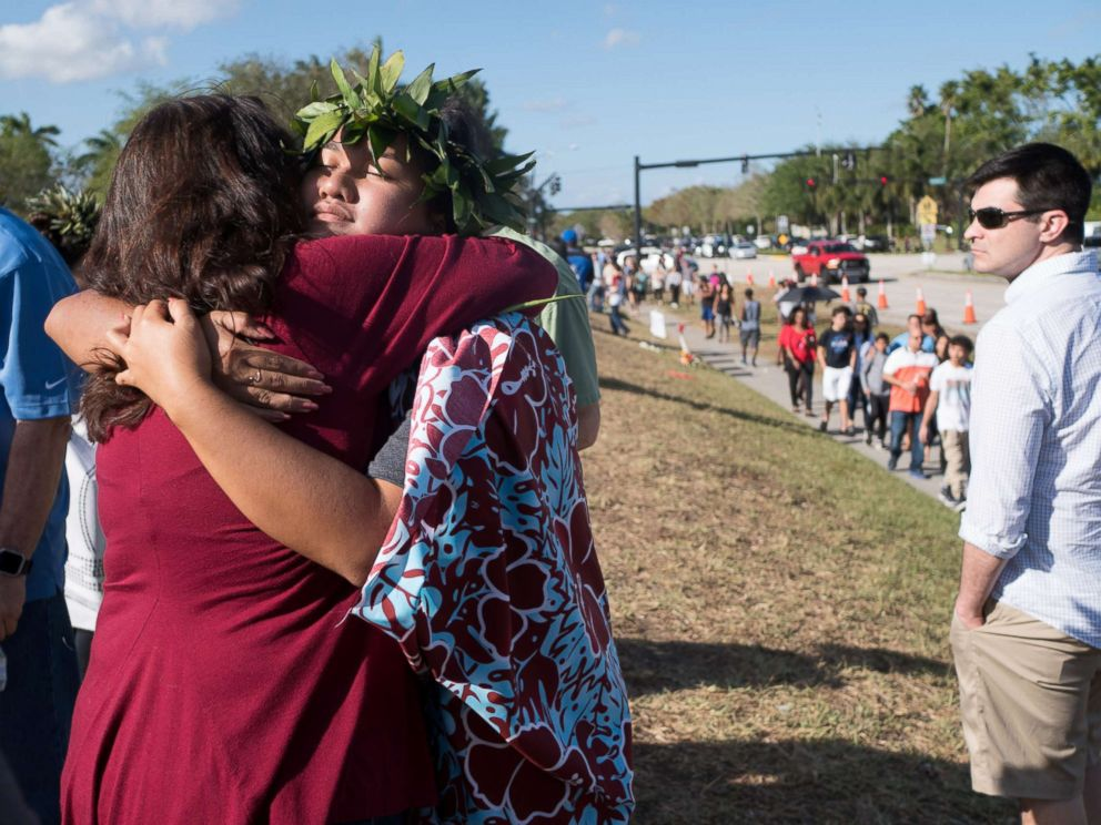 PHOTO: People embrace as students and parents arrive for voluntary campus orientation at the Marjory Stoneman Douglas High School, for the coming Wednesdays reopening, following last weeks mass shooting in Parkland, Fla., Feb. 25, 2018.