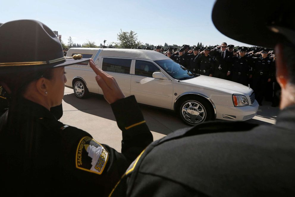 PHOTO: Law enforcement officers salute the hearse carrying the casket of Sacramento Police Officer Tara OSullivan to the Bayside Adventure Church for memorial services in Roseville, Calif., June 27, 2019.