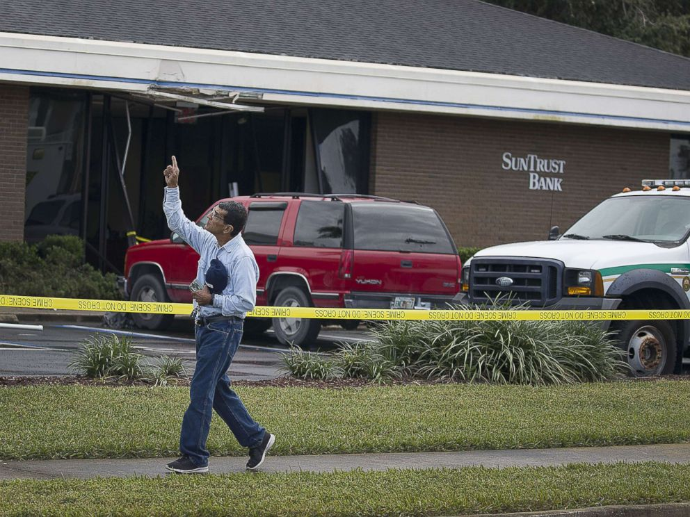 PHOTO: Jose Sanchez points to the sky as he walks in front of the SunTrust Bank branch where he said his friend was killed yesterday along with four other people on Jan. 24, 2019 in Sebring, Fla.