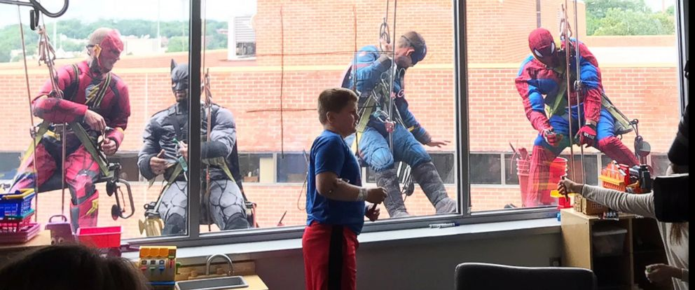 PHOTO: As the team, wearing superhero costumes, cleaned the hospitals windows, they also played games with the children at Blank Childrens Hospital in Des Moines, Iowa, June 26, 2018.