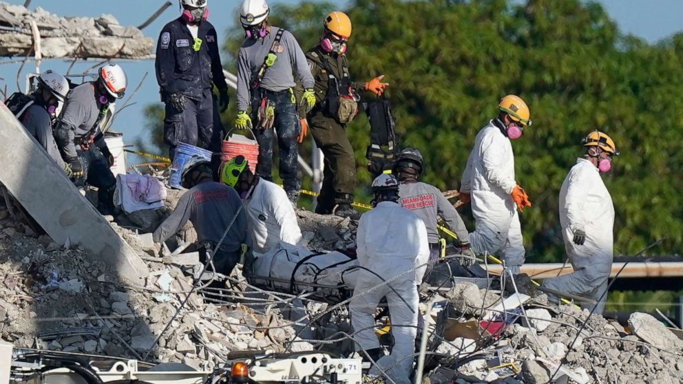 PHOTO: Search and rescue personnel remove remains on a stretcher as they work atop the rubble at the Champlain Towers South condo building where scores of people remain missing more than a week after it partially collapsed, July 2, 2021, in Surfside, Fla.