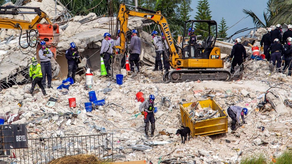 Rescuers search for victims at a collapsed South Florida condo building, July 5, 2021, in Surfside, Fla., after demolition crews set off a string of explosives that brought down the last of the Champlain Towers South building in a plume of dust on Sunday.