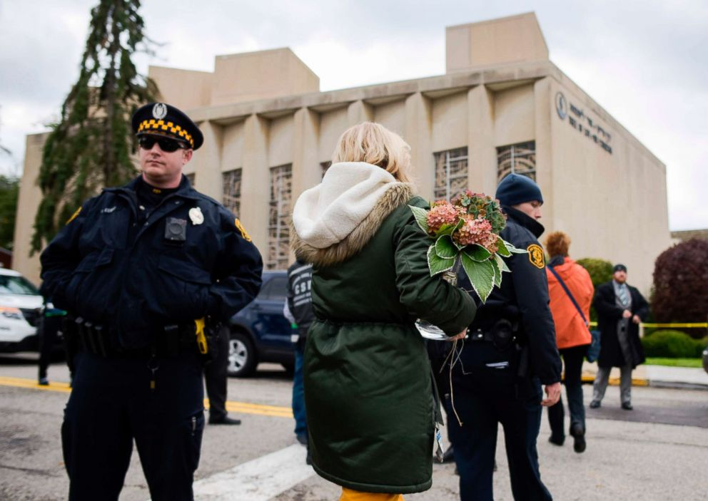 PHOTO: A woman brings flowers to a memorial, Oct. 28, 2018, near the Tree of Life synagogue after a shooting there left 11 people dead in Pittsburgh, Oct. 27, 2018.