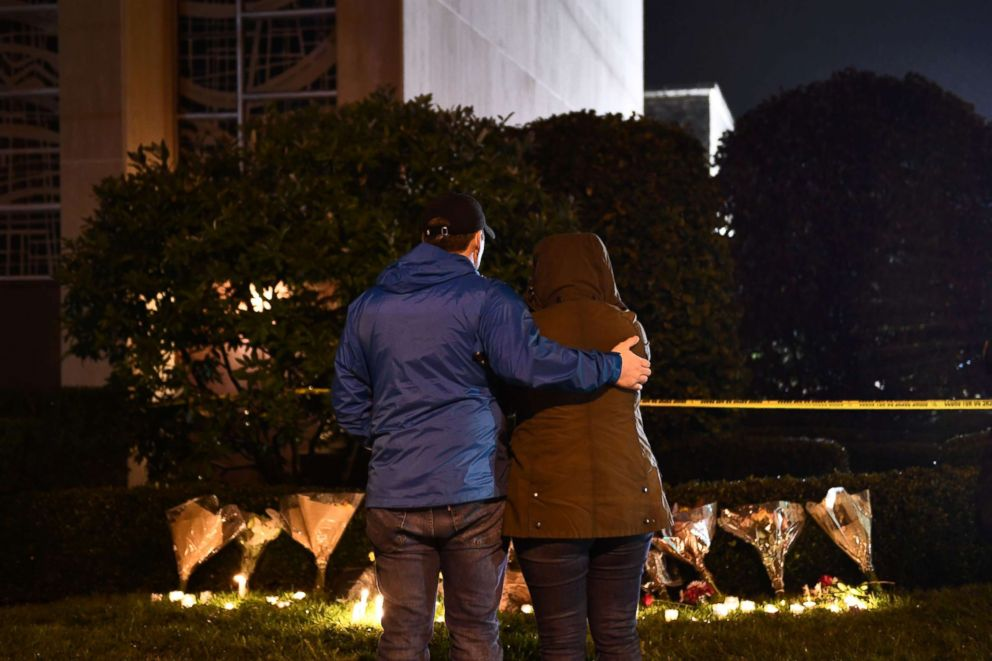 PHOTO: People stand in front of flowers and candles placed below a police cordon outside the Tree of Life Synagogue after a fatal shooting in Pittsburgh, Oct. 27, 2018.