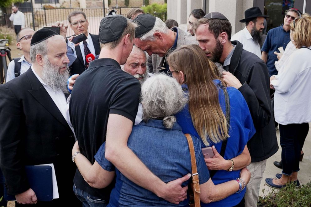 PHOTO: Executive Director Rabbi Ysrael Goldstein, center, hugs his congregants after a press conference outside the Chabad of Poway Synagogue, April 28, 2019 in Poway, Calif.