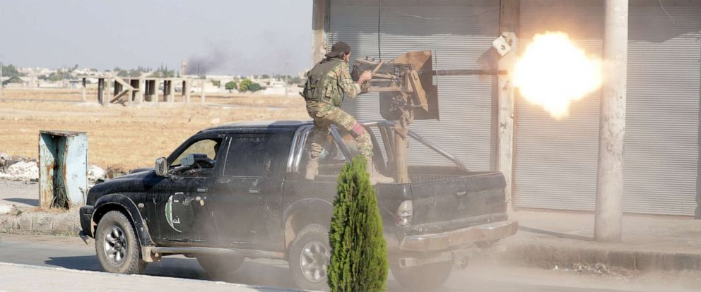 PHOTO: A Turkey-backed Syrian rebel fighter fires a weapon in the town of Tal Abyad, Syria, Oct. 13, 2019.