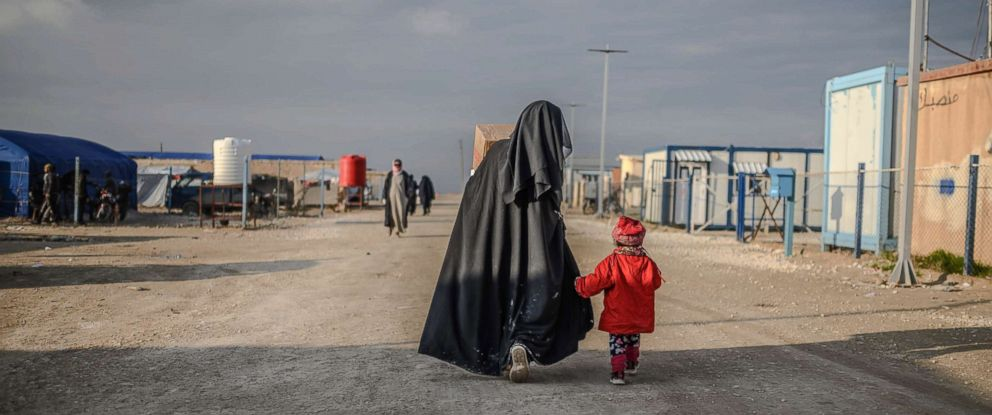 PHOTO: A veiled woman walks with her child at al-Hol camp in al-Hasakeh governorate in northeastern Syria, Feb. 17, 2019.