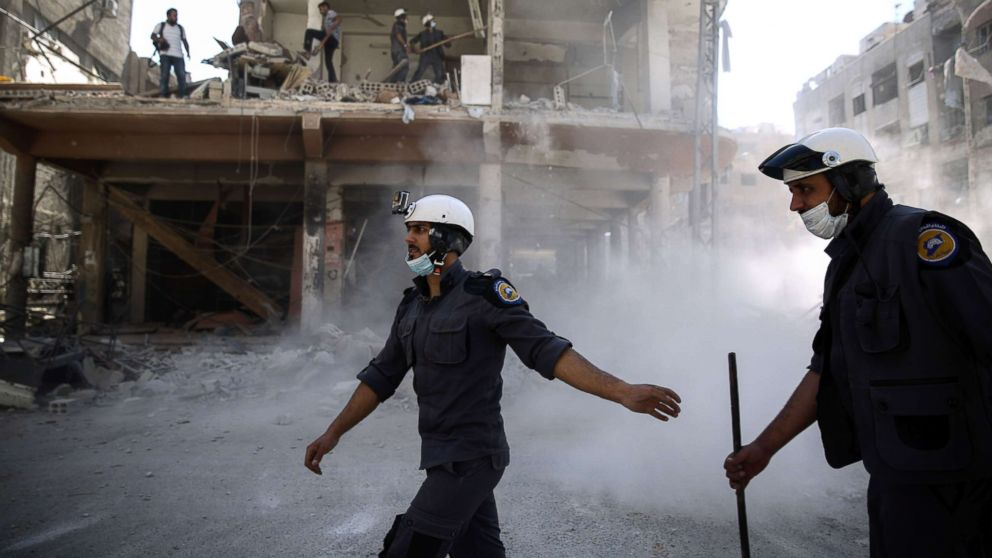 Syrian civil defense volunteers, known as the White Helmets, work around destroyed buildings following reported air strikes on the rebel-held town of Douma, on the eastern outskirts of the capital Damascus, Oct. 5, 2016.