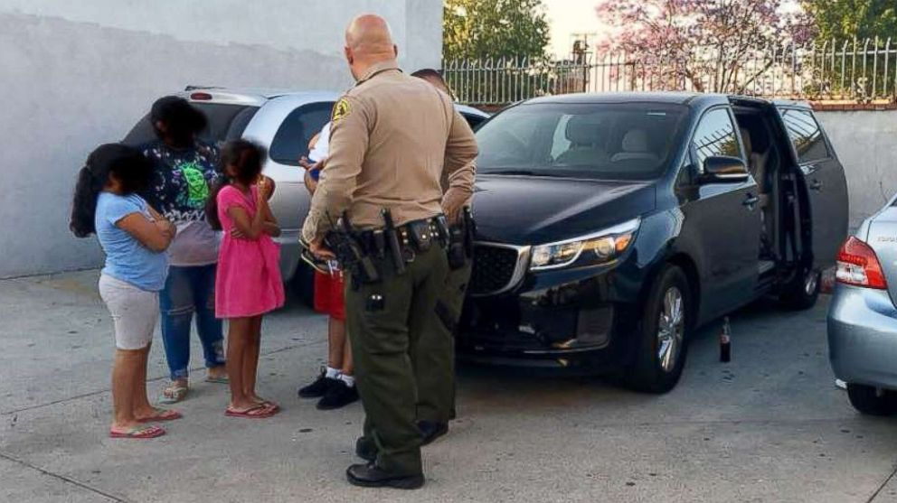 A family of six that was accosted by an armed man while eating a meal in a vehicle parked in City of Industry, Calif., June 10, 2018 is pictured speaking to law enforcement.