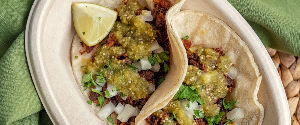 PHOTO: Two soft tacos garnished with green salsa.