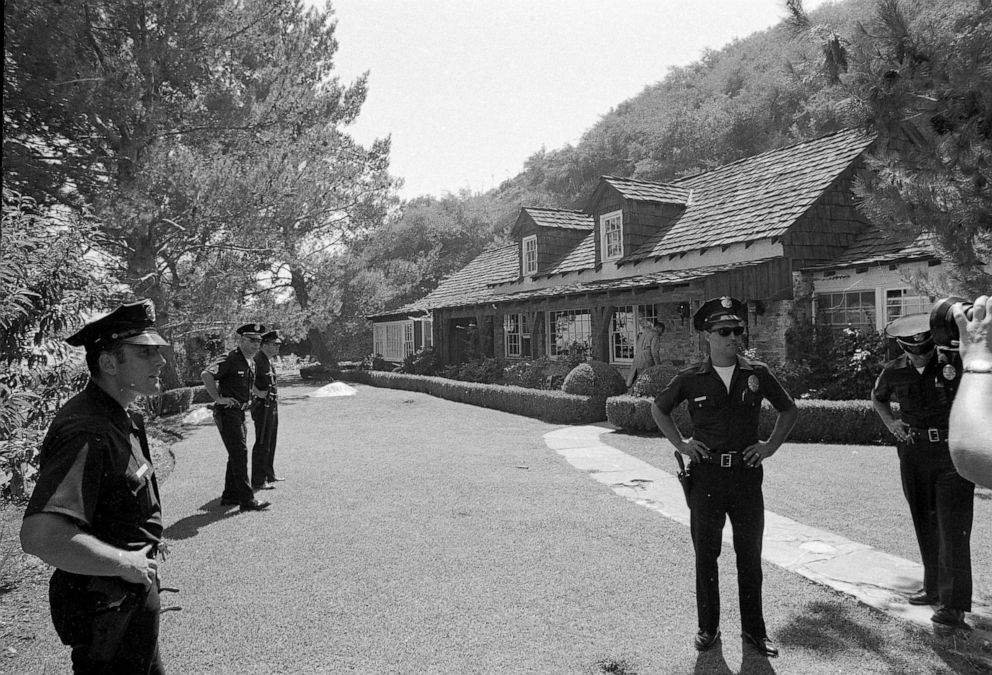 PHOTO: Police officers stand on the property of actress Sharon Tate where the bodies of five persons, including Tate, were found murdered by members of the Manson cult family, Aug. 9, 1969.
