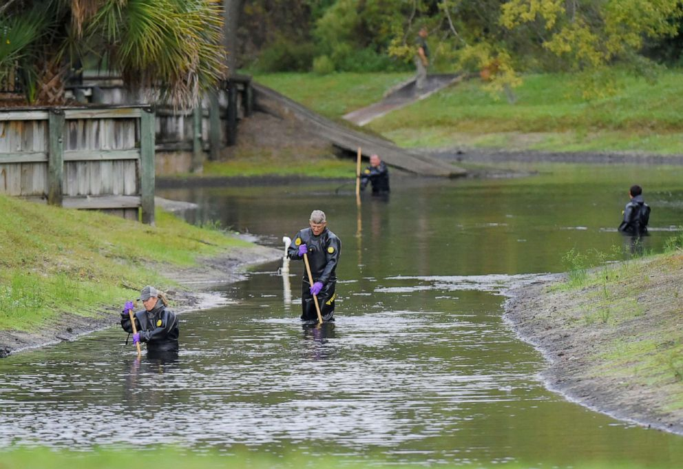 PHOTO: Law enforcement investigators in dry suits search the small retention pond near the entrance of the Southside Villas apartment complex off Southside Blvd. in Jacksonville, Fla., Nov. 6, 2019.