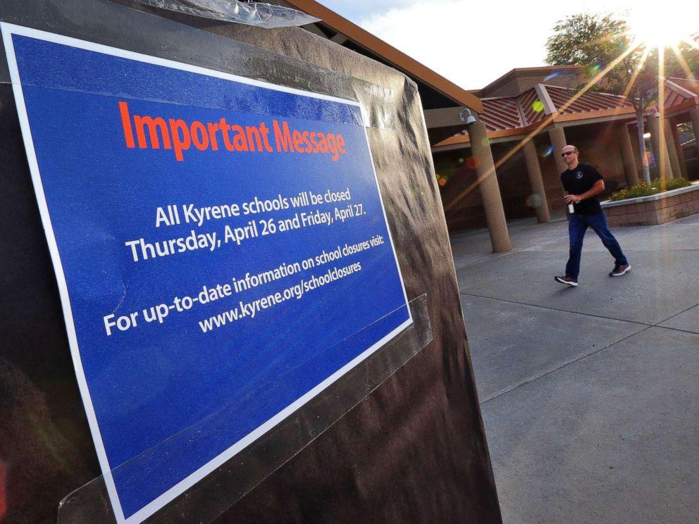 PHOTO: The sun rises over Kyrene De Las Lomas Elementary School, April 26, 2018, in Phoenix, as a teacher arrives.