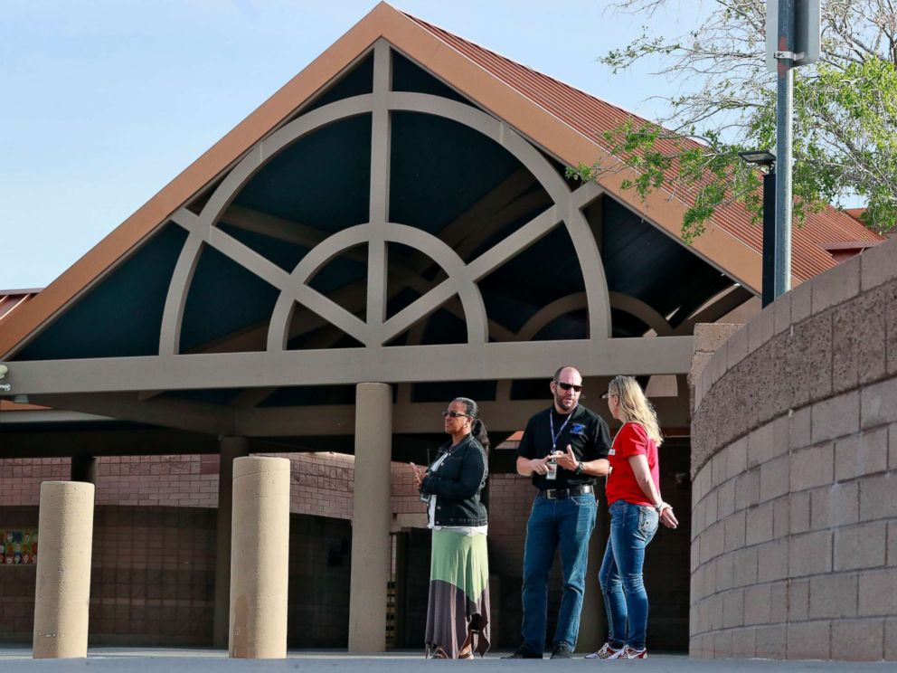 PHOTO: Principal Brian Gibson, center, and vice principal Melissa Taylor, left, stand at the entrance of Kyrene De Las Lomas Elementary School to turn students away during a teacher walkout, April 26, 2018, in Phoenix.