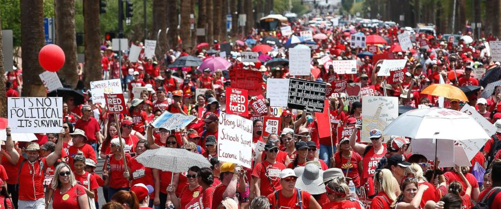 PHOTO: Thousands march to the Arizona Capitol for higher teacher pay and school funding on the first day of a state-wide teacher strike, April 26, 2018, in Phoenix.