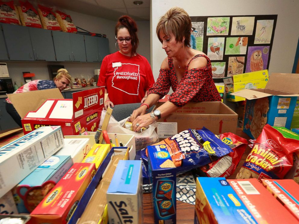 PHOTO: Highland Arts Elementary School teacher Amy Lahavich, right, organizes donated food for distribution to students and families on the eve of the teacher walk out, April 25, 2018, in Mesa, Ariz.