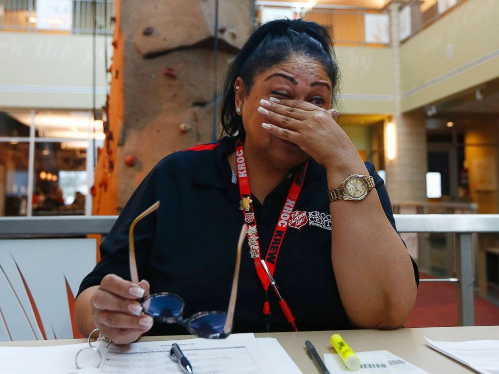 PHOTO: Special education teacher Charmaine Woods wipes away tears as she talks about not being at her teaching job in the Roosevelt School District as she checks kids in at a special day camp at the Salvation Army Kroc Center, April 26, 2018, in Phoenix.