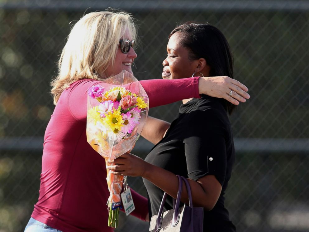 PHOTO: Marjory Stoneman Douglas High School assistant principal Denise Reed hugs a school employee as she returns to the school, Feb. 23, 2018.