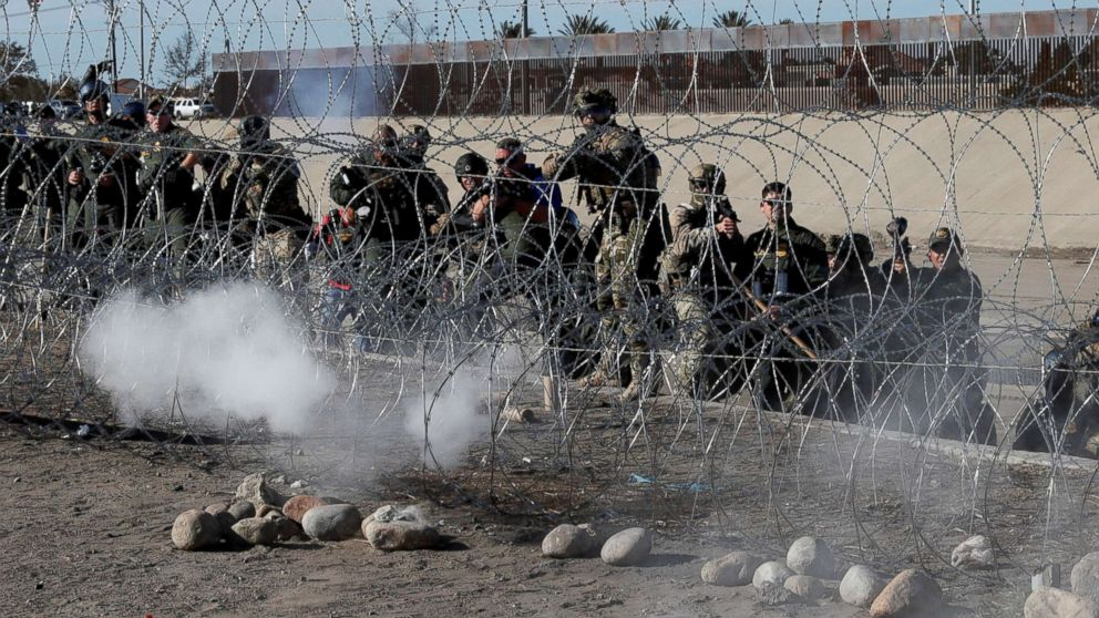 U.S. soldiers and U.S. border patrol officers fire tear gas towards migrants, part of a caravan of thousands traveling from Central America en route to the United States, from the U.S.side of the border fence between Mexico and the United States in Tijuana, Mexico, Nov. 25, 2018.