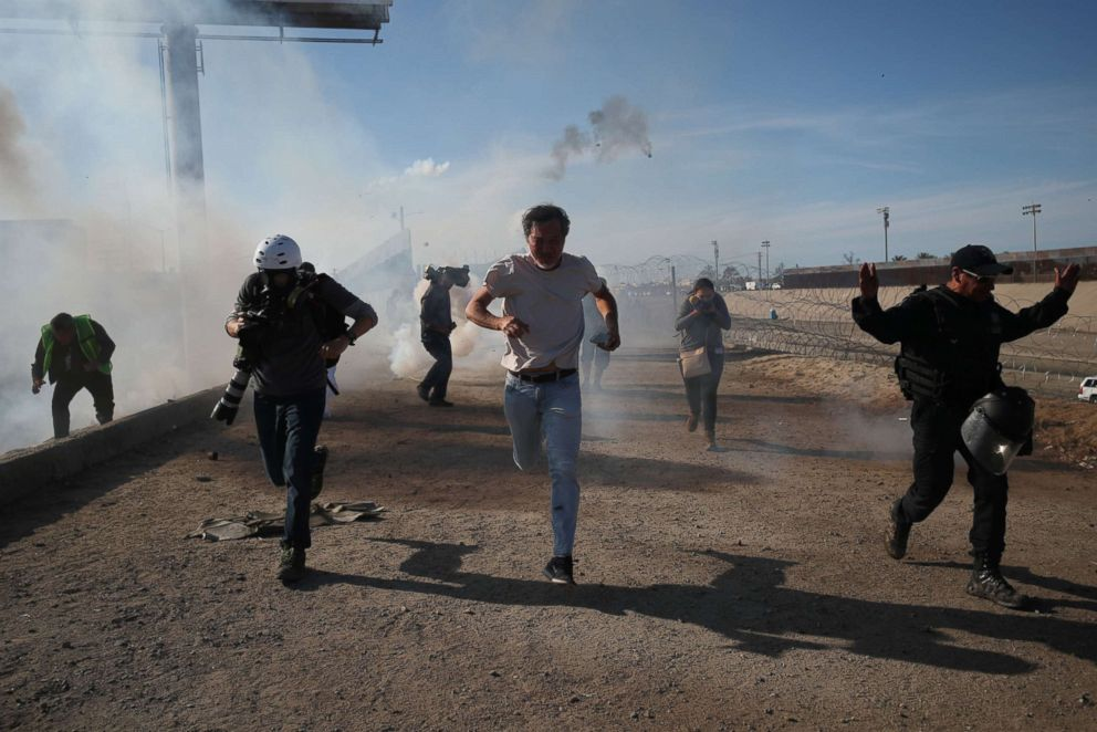Migrants and members of the media run from tear gas released by U.S border patrol near the fence between Mexico and the United States in Tijuana, Mexico, Nov. 25, 2018.