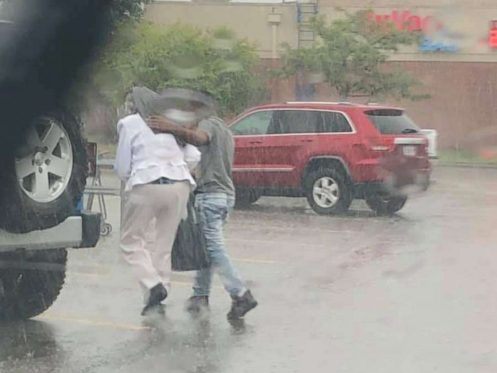 PHOTO: An officer snapped a photo of a young man getting out of his car to help shield a woman from the rain.