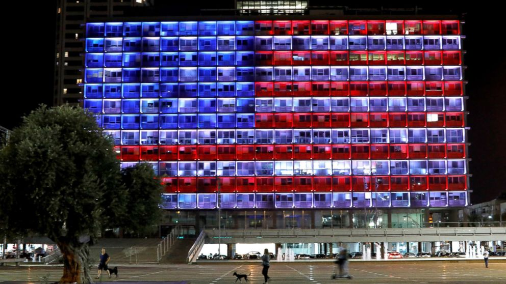 People walk by as the municipality building in Tel Aviv, Israel, is lit in the colors of the American flag in solidarity with the victims of the Pittsburgh synagogue attack, Oct. 27, 2018.