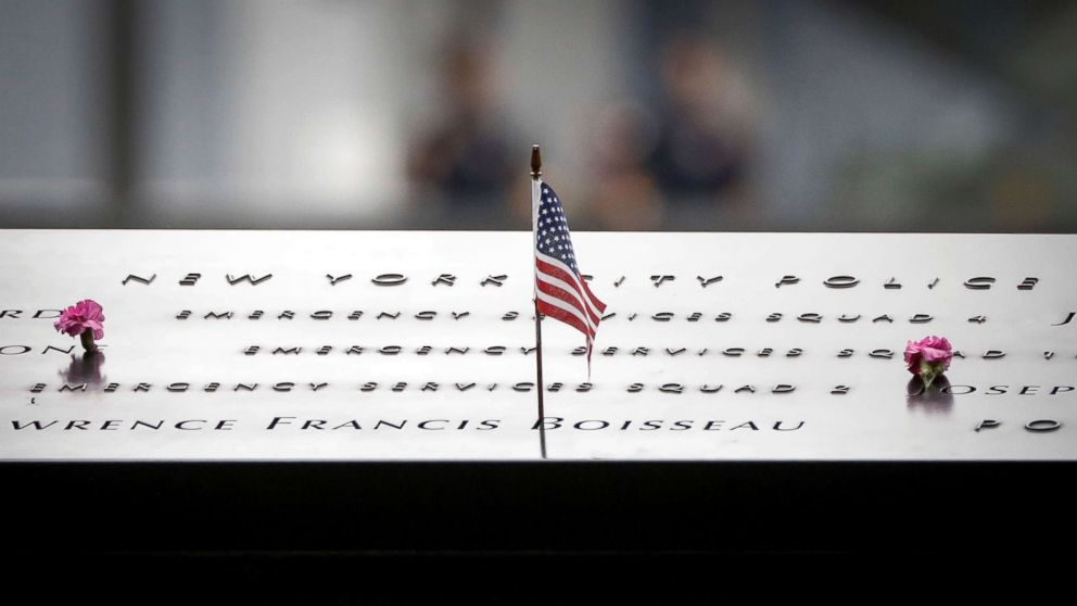Flowers and a flag are left on names at the National 9/11 Memorial during ceremonies marking the 17th anniversary of the September 11, 2001 attacks on the World Trade Center, in New York, Sept. 11, 2018.