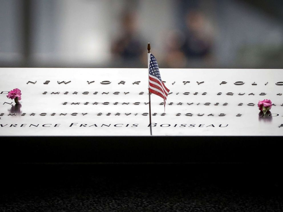 PHOTO: Flowers and a flag are left on names at the National 9/11 Memorial during ceremonies marking the 17th anniversary of the September 11, 2001 attacks on the World Trade Center, in New York, Sept. 11, 2018.