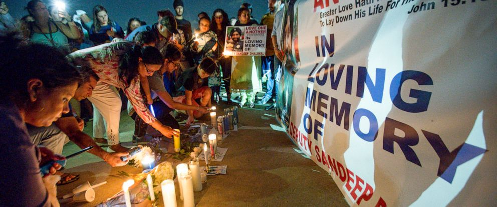 PHOTO:People lay candles at a vigil in front of a poster in honor of Harris County Sheriffs Office Deputy Sandeep Dhaliwal Houston, Texas, Sept. 30, 2019.