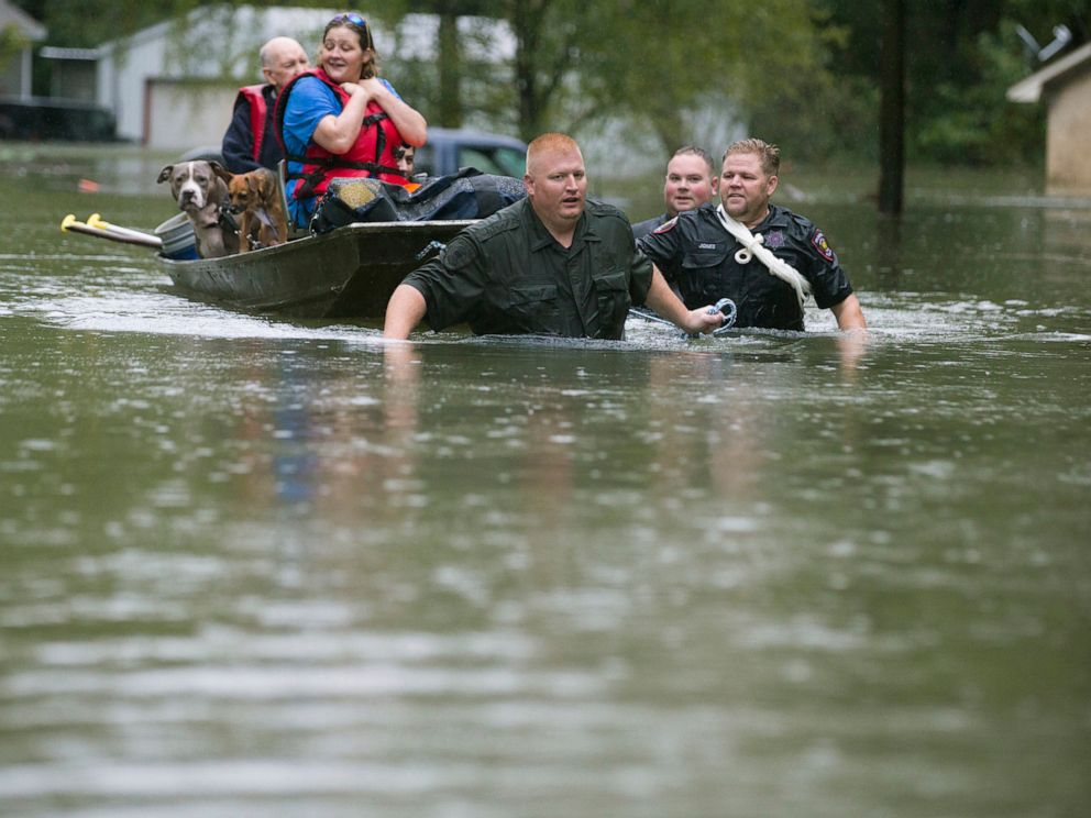 PHOTO: Splendora Police Lt. Troy Teller, left, Cpl. Jacob Rutherford and Mike Jones pull a boat carrying Anita McFadden and Fred Stewart from their flooded neighborhood on Sept. 19, 2019, in Spendora, Texas.