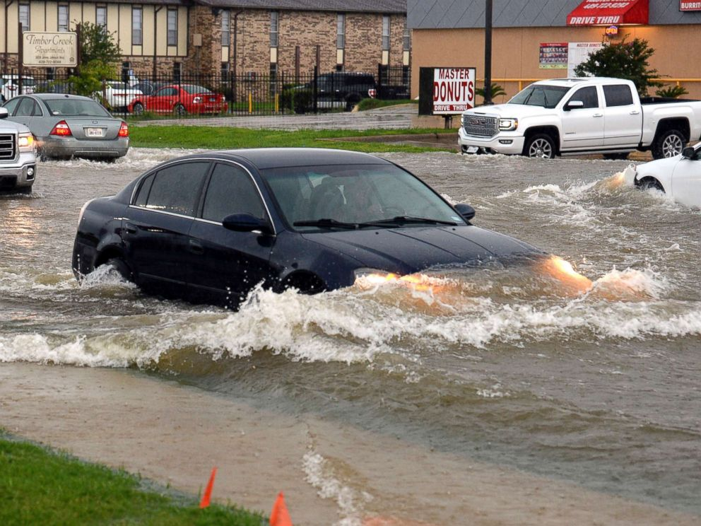 PHOTO: In this Tuesday, June 19, 2018 photo, cars push through high waters on Jimmy Johnson Boulevard during a rain storm in Port Arthur, Texas.