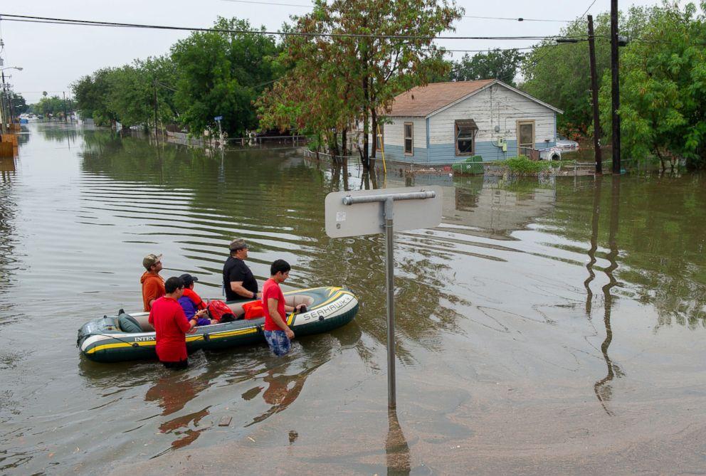 PHOTO: A woman is evacuated by volunteers in devastating floodwaters, June 20, 2018, in Weslaco, Texas.