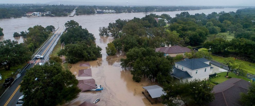 PHOTO: The Llano River overflows its banks into neighboring property as the swollen river flows between the washed out Ranch Road 2900 bridge, background, Oct. 16, 2018, in Kingsland, Texas.