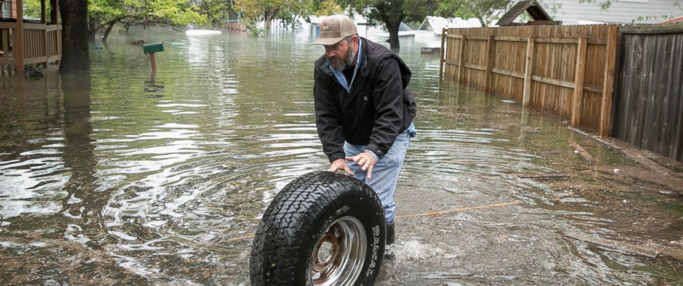 PHOTO: Stuart Cooper retrieves his fathers belongings from the floodwaters in the Graveyard Point neighborhood on Lake Travis on Wednesday, Oct. 17, 2018, in Austin, Texas.