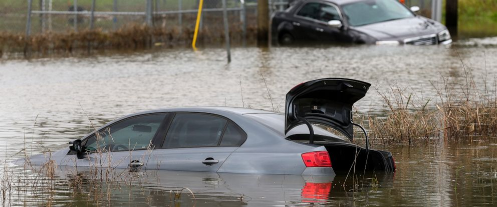 PHOTO: Two vehicles remain stuck in flooded Adams Street following an overnight storm Wednesday, May 8, 2019, in Porter, Texas.