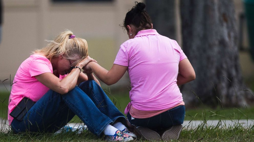 Two women pray outside the family reunification site following a shooting at Santa Fe High School on May 18, 2018, in Santa Fe, Texas.