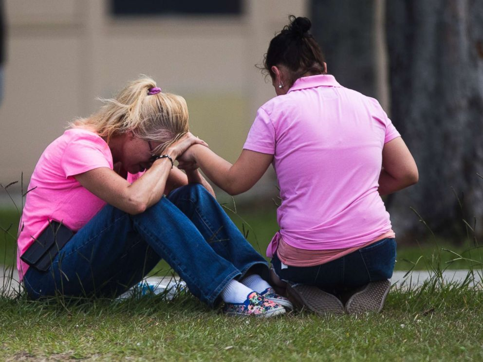 PHOTO: Two women pray outside the family reunification site following a shooting at Santa Fe High School on May 18, 2018, in Santa Fe, Texas.