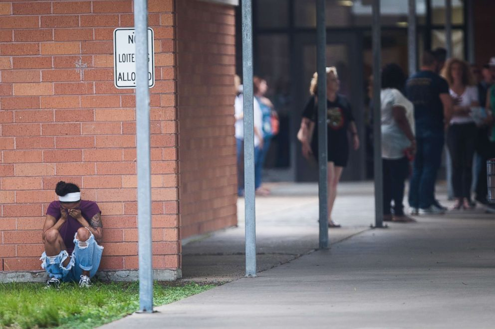 PHOTO: People gather by the Barnett Intermediate School where parents are gathering to pick up their children following a shooting at Santa Fe High School on May 18, 2018, in Santa Fe, Texas.